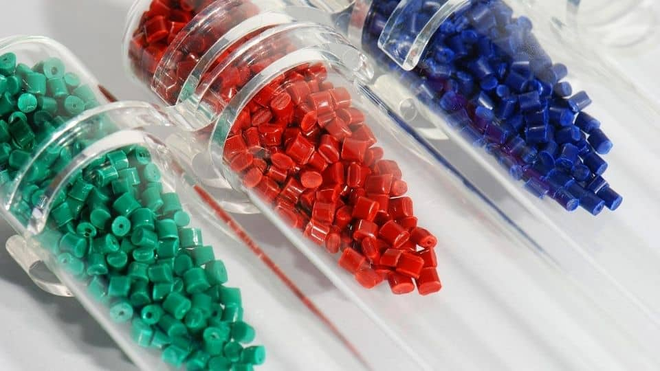 Dyed polymer resin in test-tubes in labortory, nurdles, small plastic pellets
